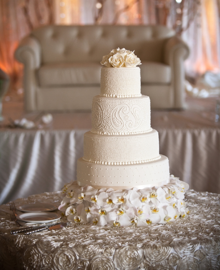 Orchids, textured tablecloth, and gold and white mandap offset this ivory paisley wedding cake