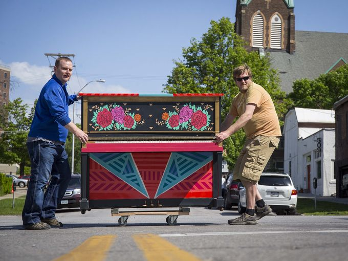 West Music's Jeff Weimar and Tony Grimm, right, roll a piano up Grand Ave. in the East Village for City Sounds: Des Moines Public Piano Project Thursday May 19, 2016.   Photo by Rodney White / The Register.