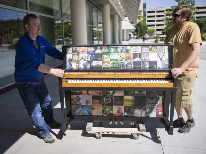 West Music's Jeff Weimar, left, and Tony Grimm roll a decorated piano into position in Cowles Commons for the City Sounds Public Piano Project. Thursday May 19, 2016.   Photo by Rodney White / The Reigister.