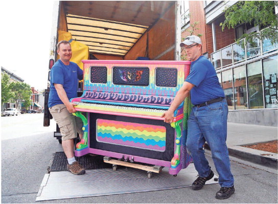 Jeff Weimar (left) and Adam Miller with West Music unload the first of 10 pianos they are placing around downtown Des Moines on Tuesday outside of RAYGUN in the East Village. The pianos were installed as part of City Sounds' annual public piano project, and will be in place through late September.