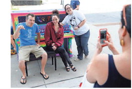 RAYGUN owner Mike Draper (from left), RAYGUN head designer Jennifer Leatherby and Jennifer Boes with City Sounds, take a photo together Tuesday in front of the cat-themed piano installed in front of the East Village store.