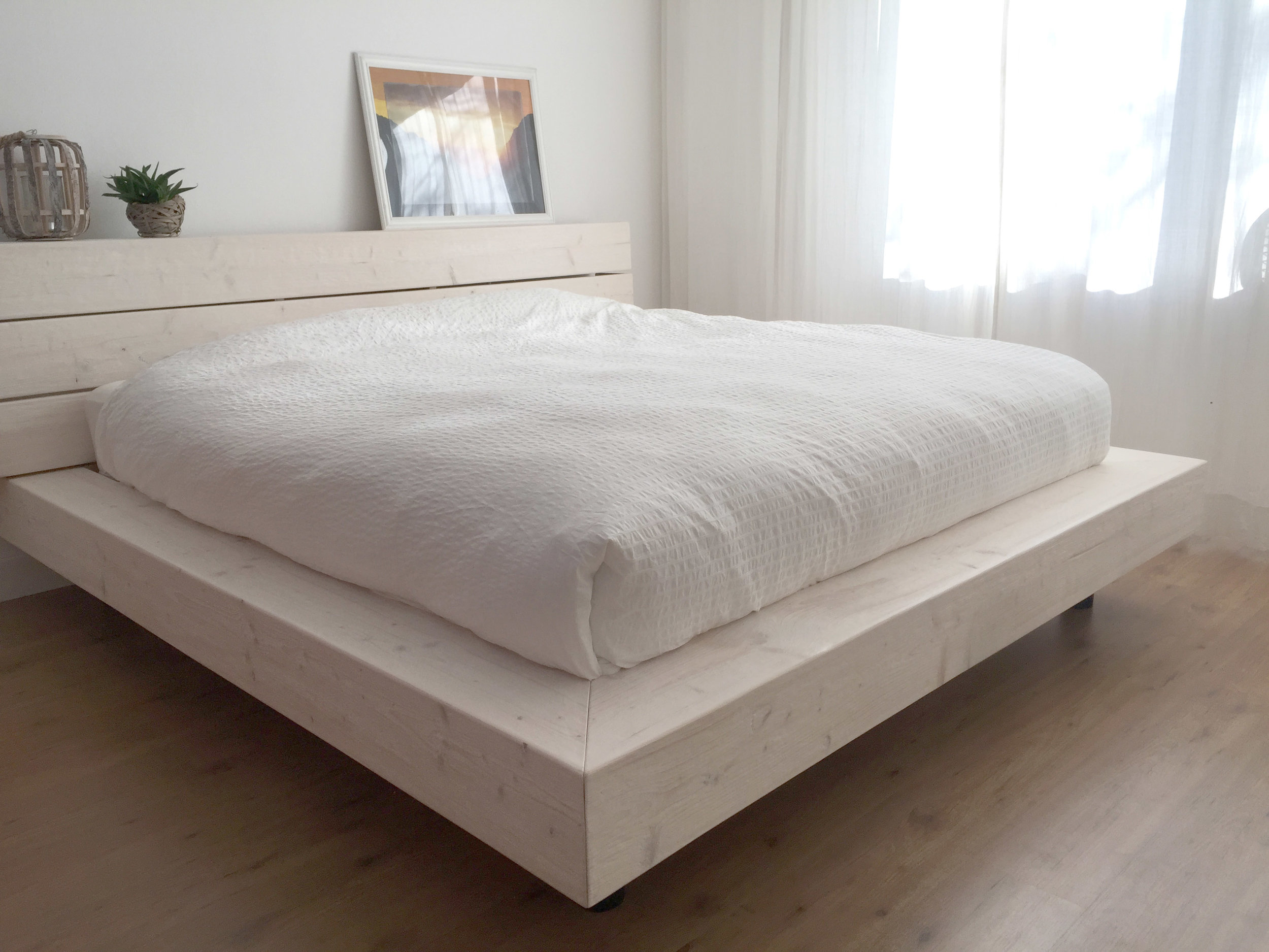 Robuust bed met een dikke matras en wit beddengoed.