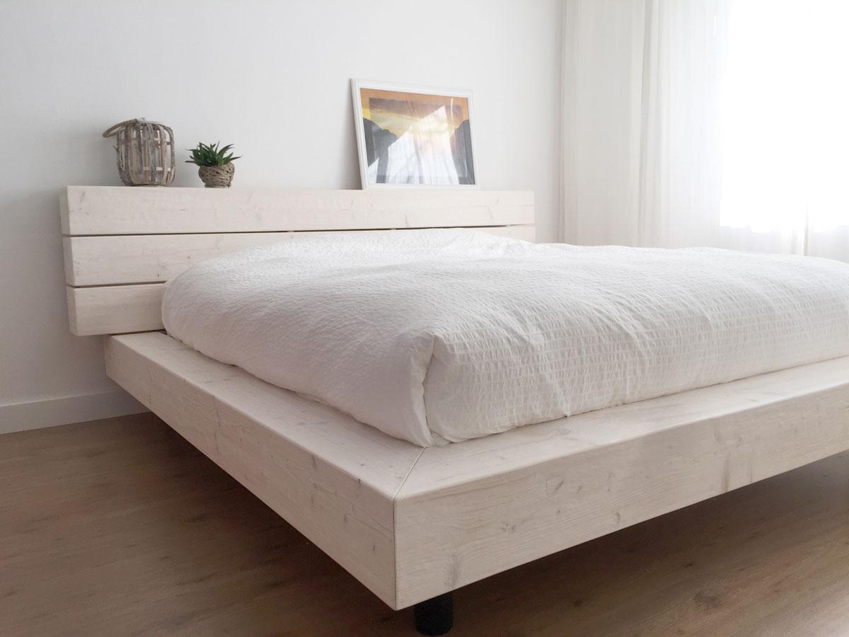 Robuust houten bed met dikke balken.