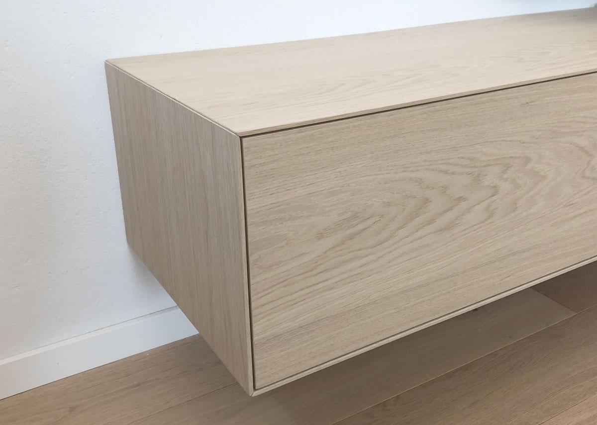 Afbeelding van een op verstek verlijmd eiken gefineerd meubel met een minimalistische vormgeving.