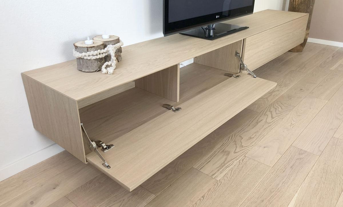 Afbeelding van een eiken gefineerd TV meubel met een opengeklapte klep zodat scharnieren en klephouder zichtbaar zijn.