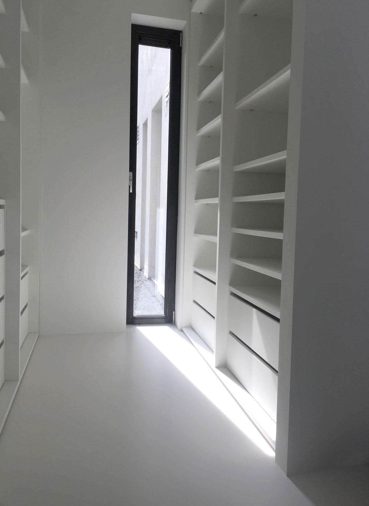 Afbeelding van een design kledingkast op maat zonder deuren, men ziet lades en legplanken, zonlicht schijnt subtiel de ruimte in.