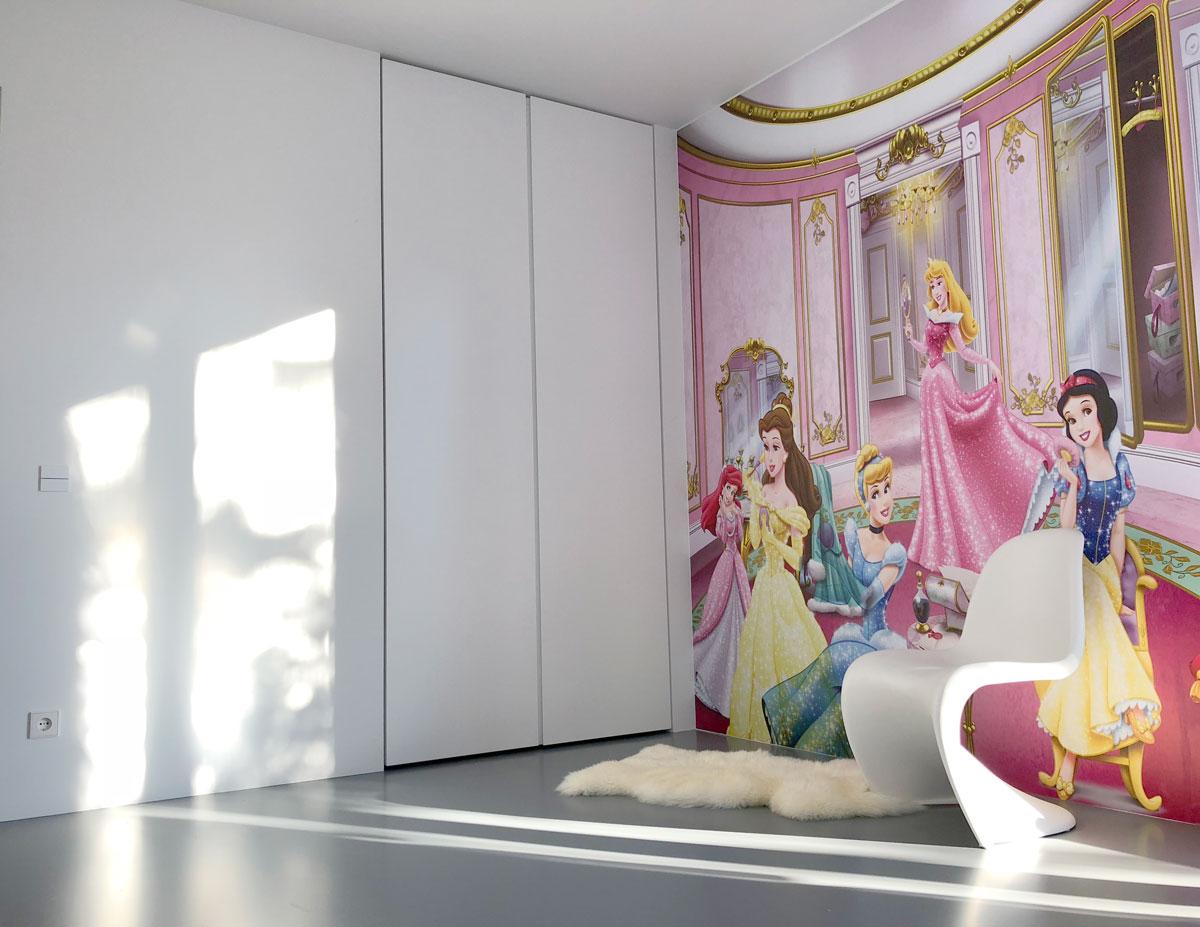 Afbeelding van een ultra mat witte design kinderkledingkast op maat met een posterbehang op de muur van Disneyfiguren.