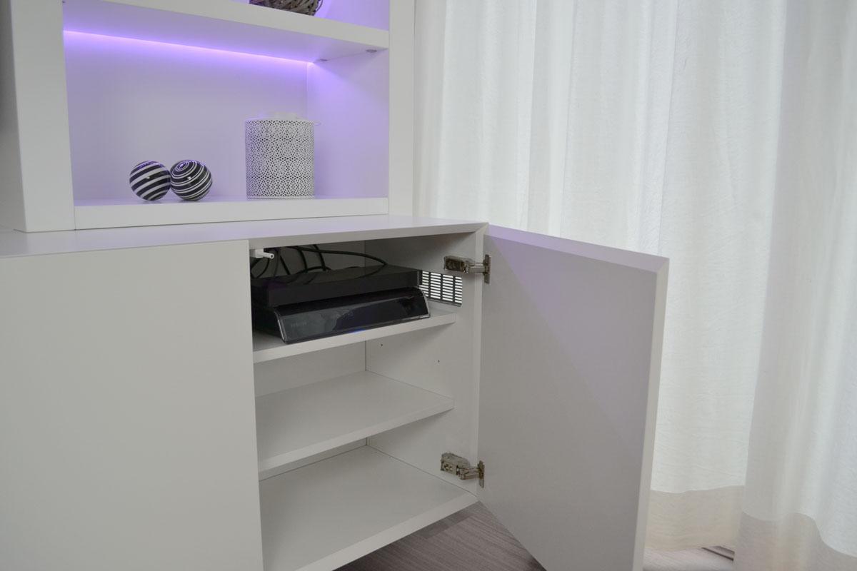 Afbeelding van apparaten en een ventilatierooster in een wit TV meubel.