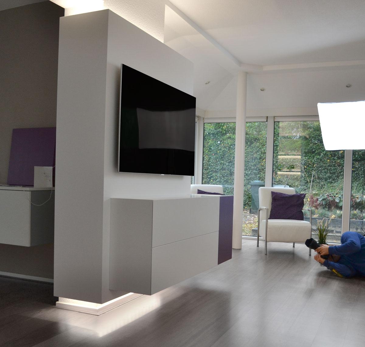 Afbeelding van een hoek design TV meubel om een zuil met op de achtergrond een fotograaf op de vloer.