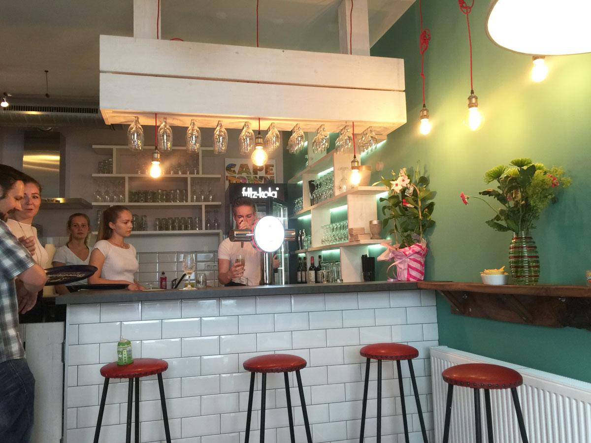 Afbeelding van een café en bar met gasten en barpersoneel op de achtergrond.