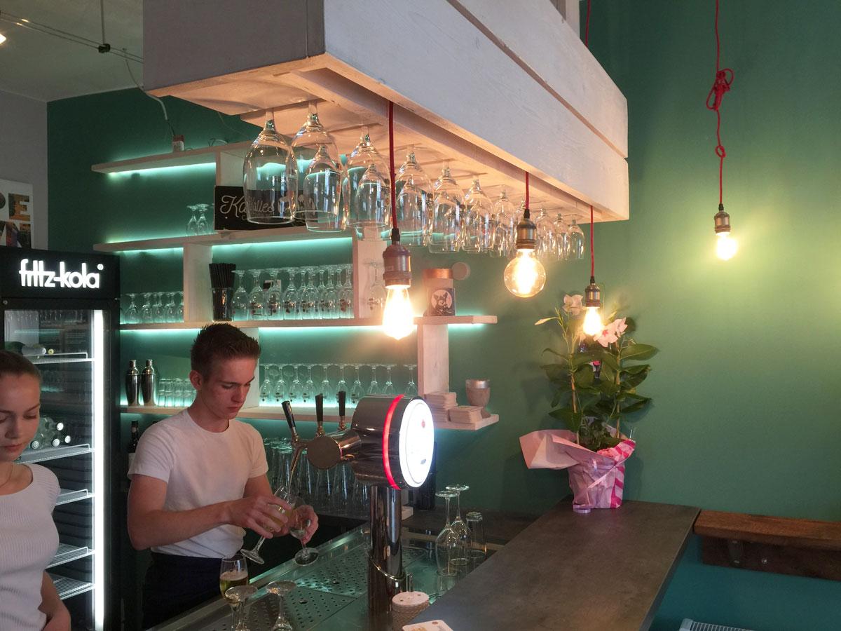 Afbeelding van een café en bar met steigerhout meubels waar wijnglazen in hangen.