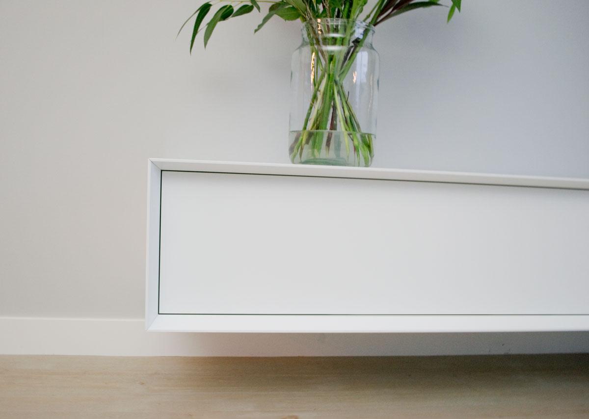 Afbeelding van een afgeschuinde kant van een wit TV meubel.