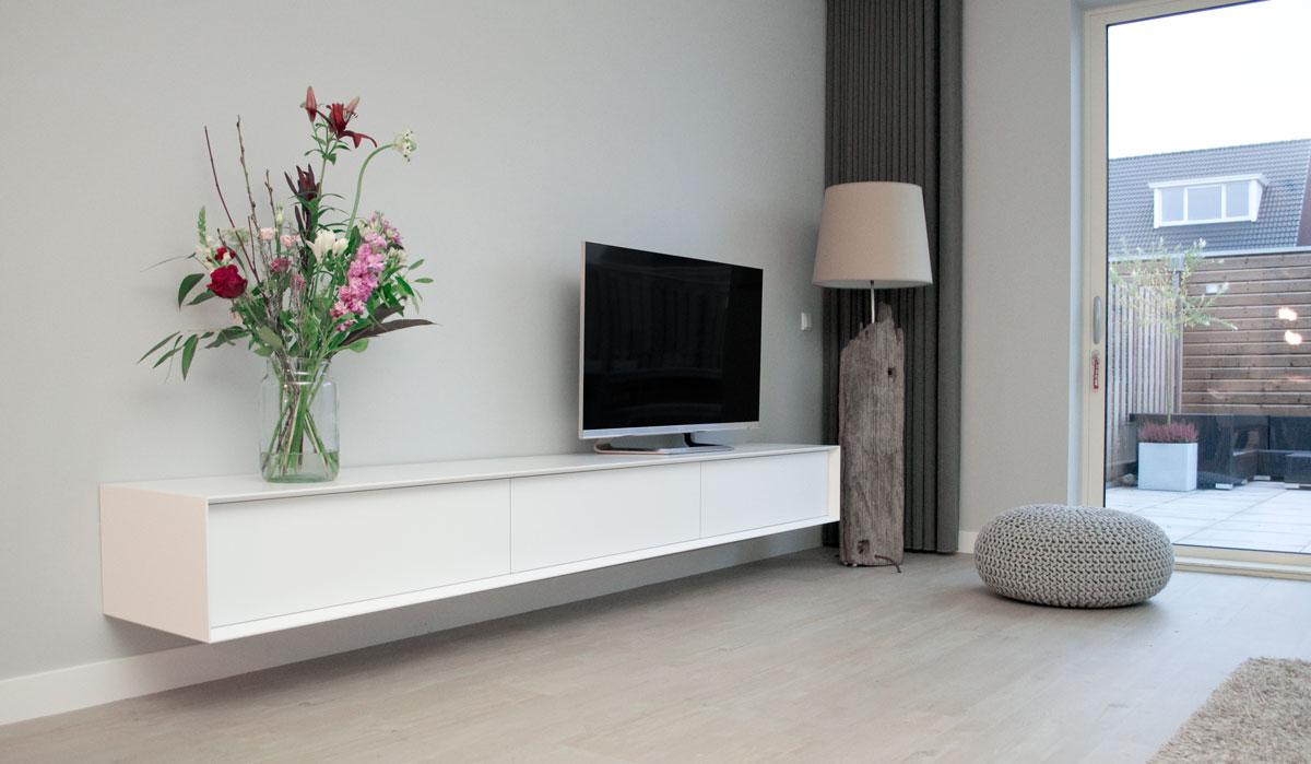 Afbeelding van een wit TV meubel met een afgeschuinde rand in een modern interieur.