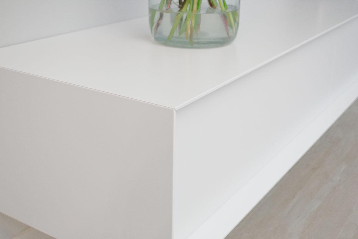 Detailafbeelding van een op verstek verlijmde hoek van een wit design TV meubel.