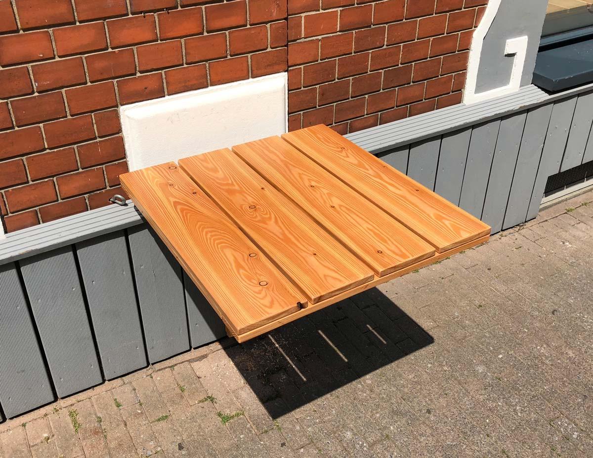 Afbeelding van een blank gelakte massief houten outdoor klaptafel van boven gefotografeerd,