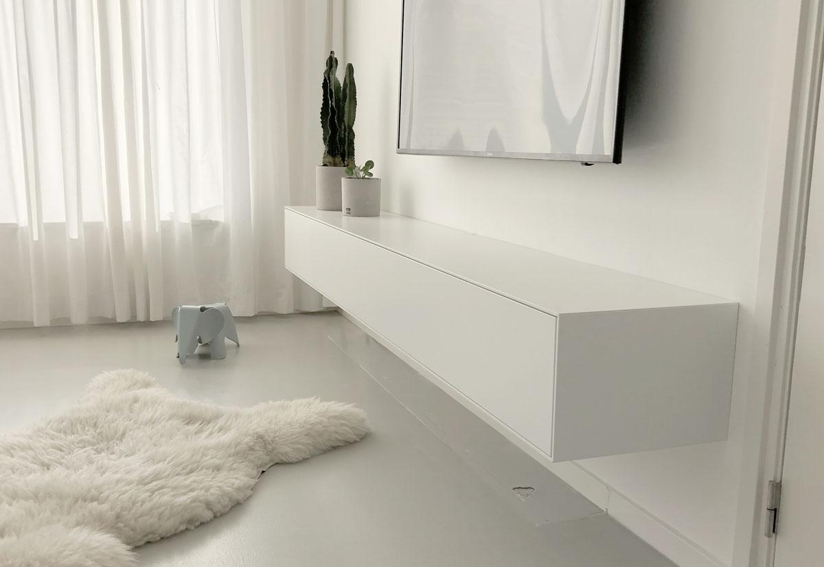 Afbeelding van een minimalistisch mat wit TV meubel met een namaak berenvel op een grijze gietvloer.