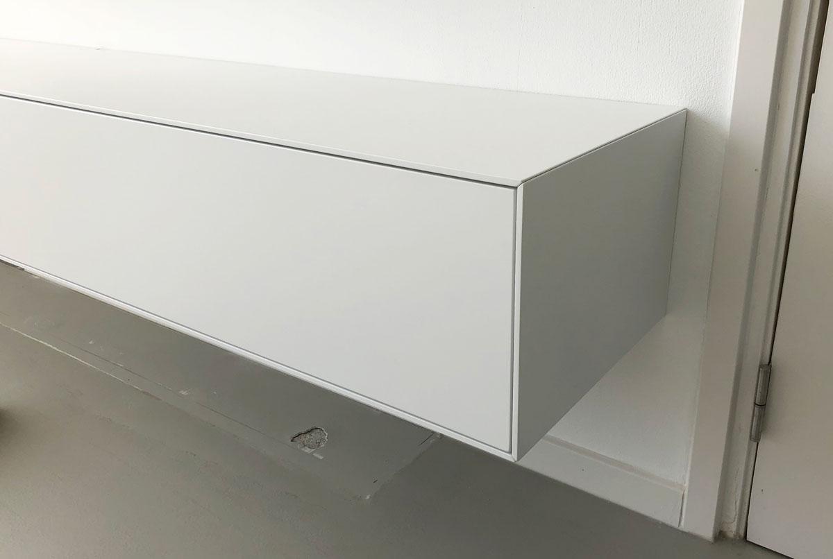 Detail afbeelding van de fijne afwerking van een minimalistisch vormgegeven wit TV meubel.