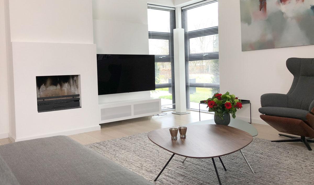 Afbeelding van een TV meubel aan een wandpaneel in een interieur met salontafels, kleed en bloemen.