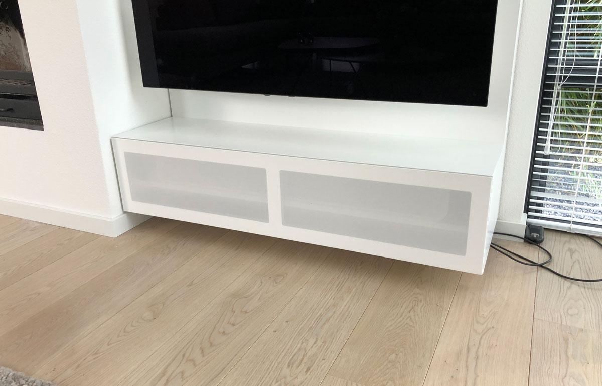 Afbeelding van een minimalistische gesloten luidsprekerklep in een wit TV meubel.