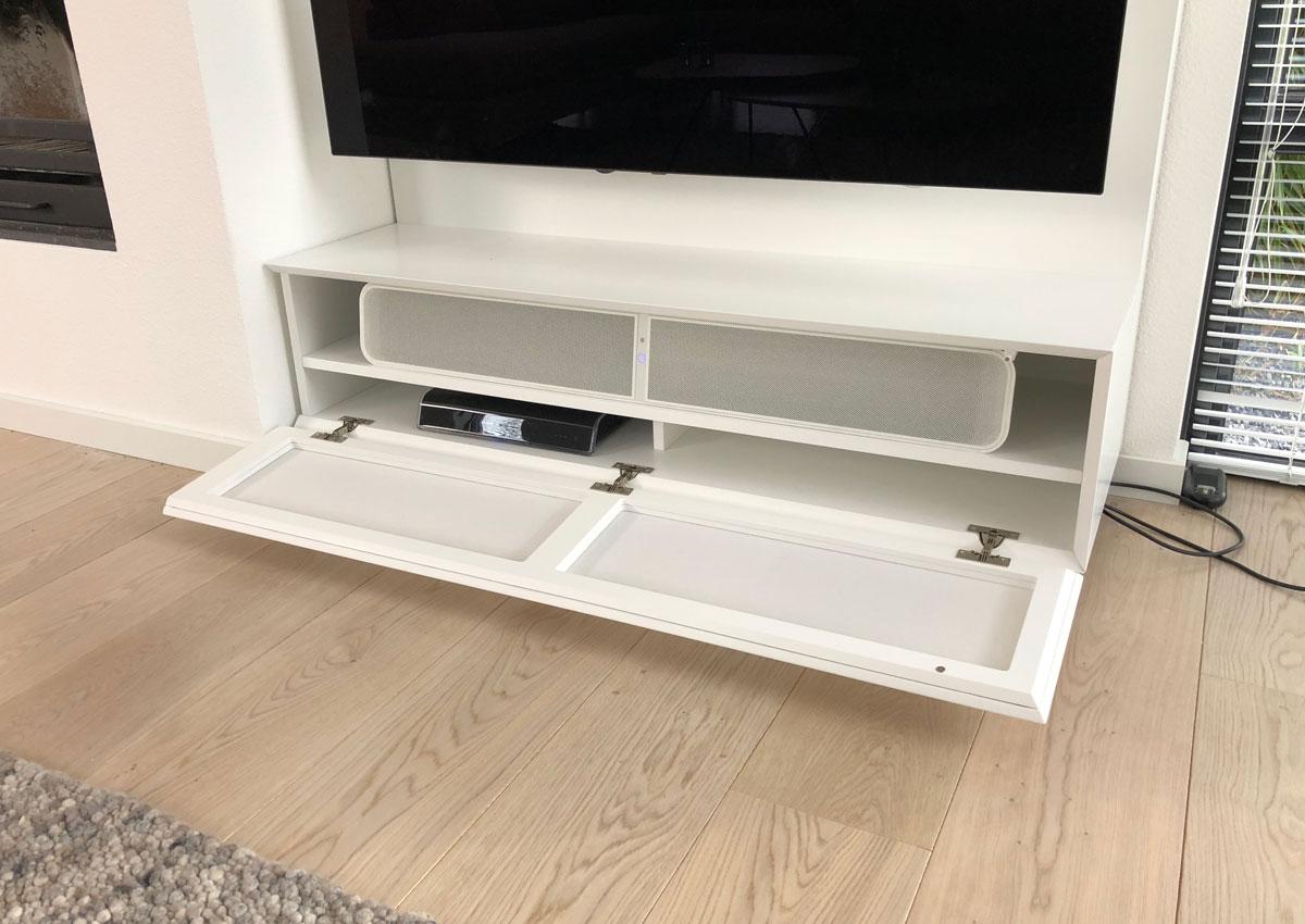 Afbeelding van een minimalistische geopende luidsprekerklep in een wit TV meubel.