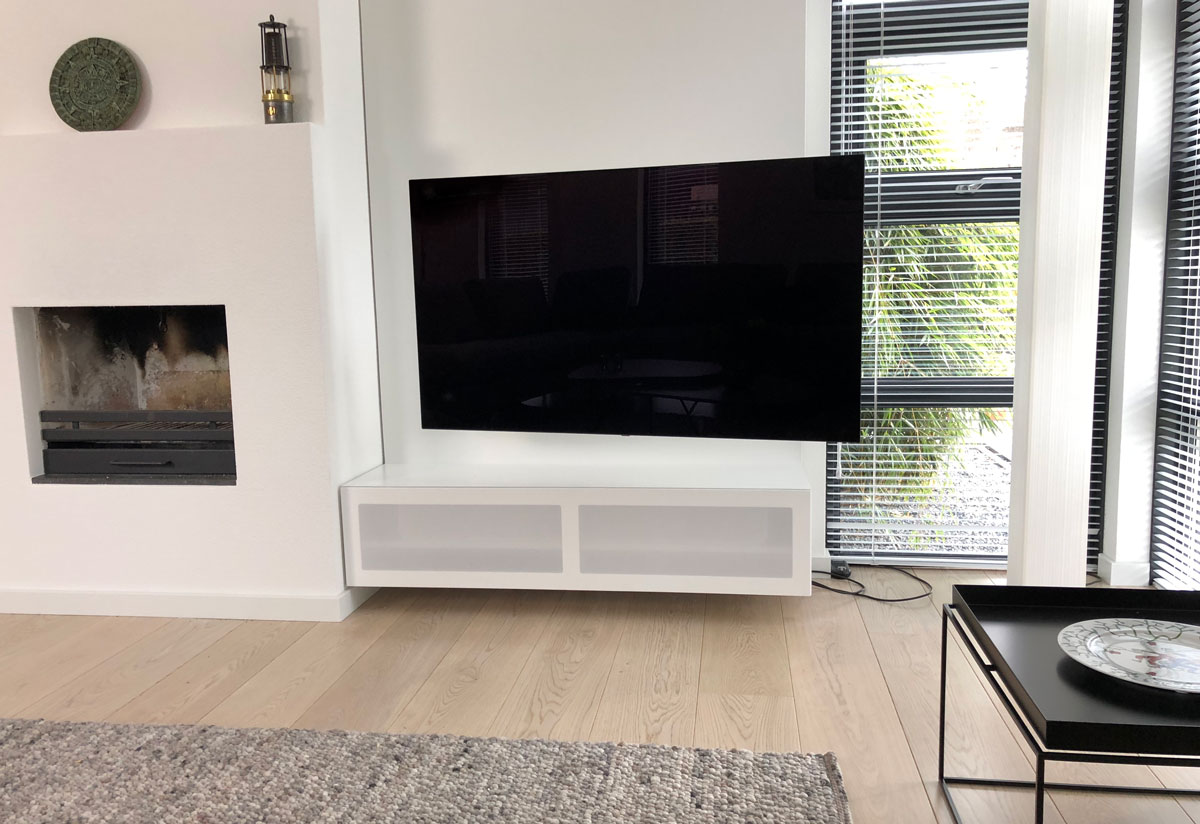 Afbeelding van een draaibare TV arm beugel aan een wandpaneel TV meubel.