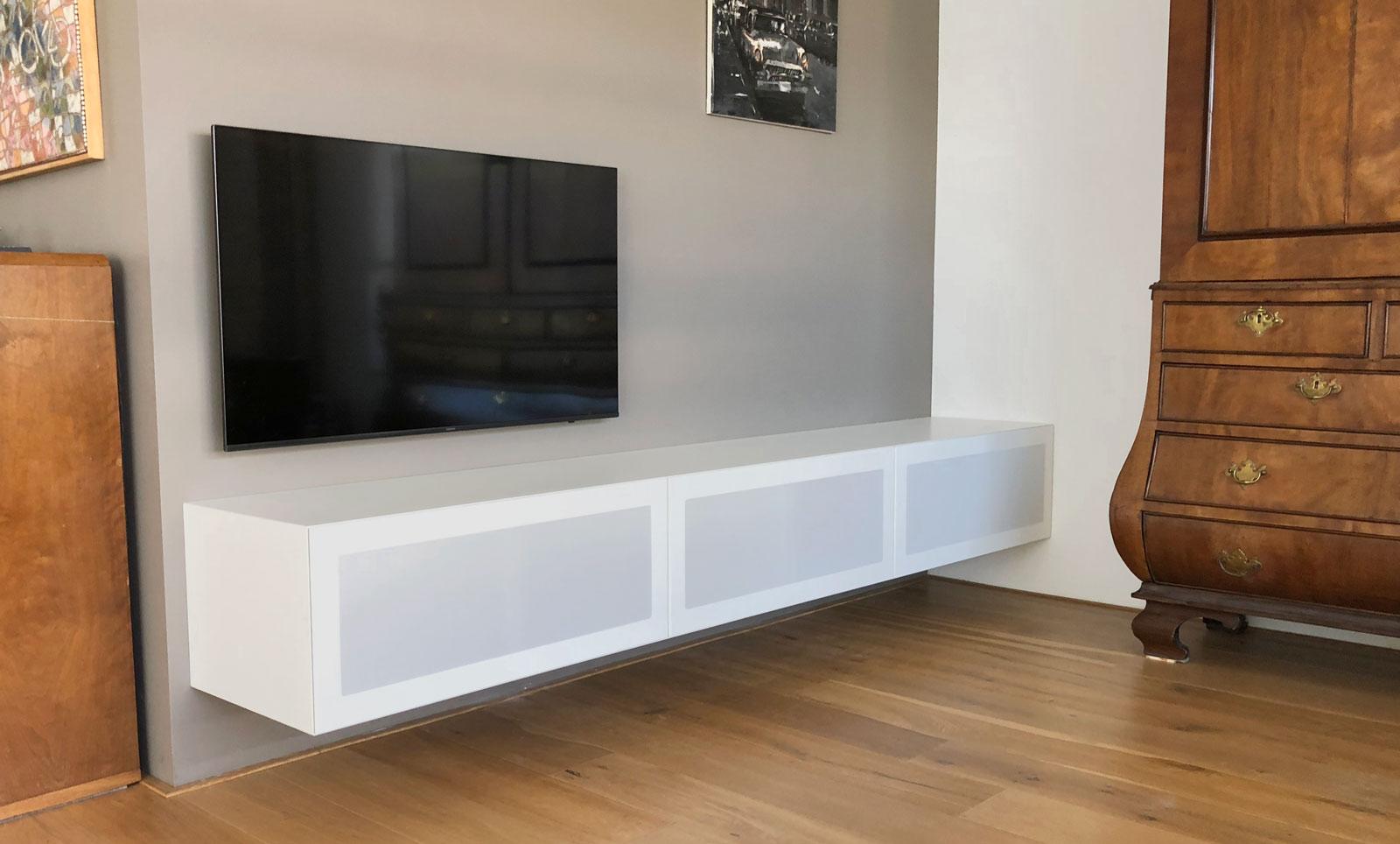 Afbeelding van een wit tv meubel op verstek met luidsprekerdeuren in een houten interieur.