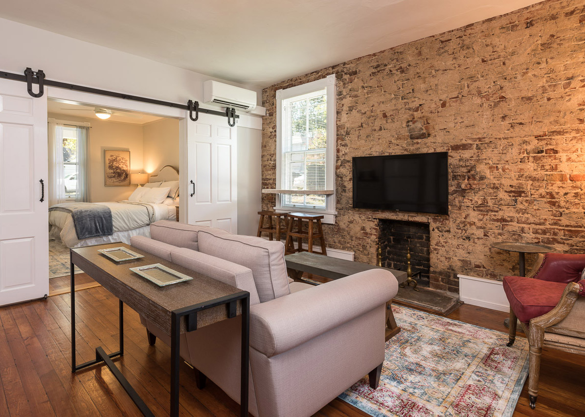 French Cottage - This first-floor apartment has exposed brick, antique heart pine floors, 9' ceilings, large barn doors, a farm sink, and apple crate kitchen drawers blended with a soft, romantic decor.