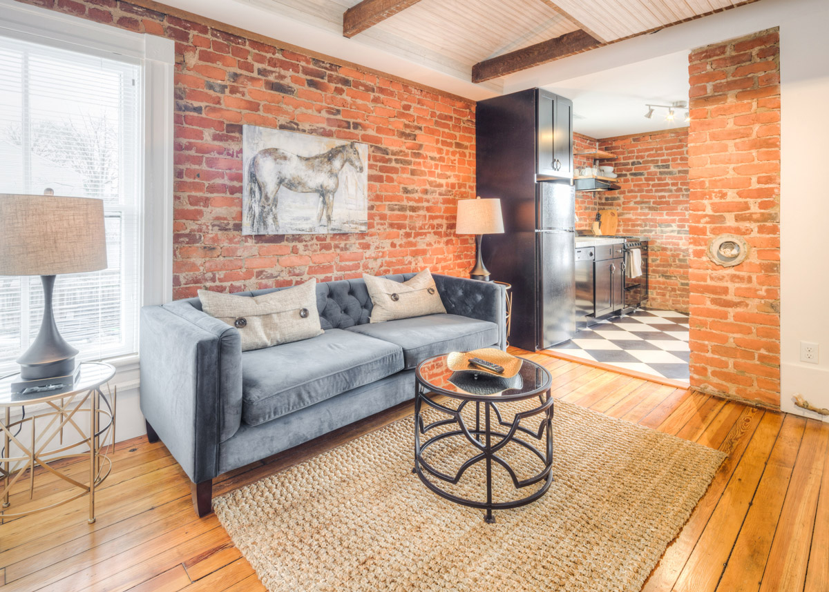 The Elegant - This second-story apartment is the perfect juxtaposition of chic comfort and classic modern style. The Elegant features a full kitchen with concrete countertops and black and white diamond-shaped floors, exposed brick, 9' ceilings, original heart pine floors, and a chic living area.