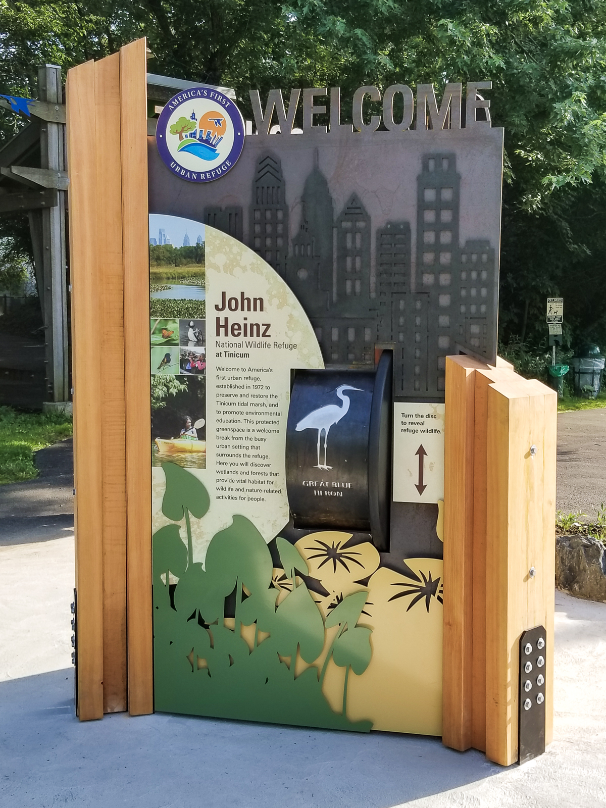This three-sided outdoor welcome structure includes cut metal, graphics, and interactives.