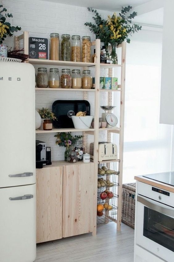 - Once again, let's swoon over the Smeg fridge. But moving on. This is so perfect for a smaller kitchen. In fact, if we didn't have our pantry now, I would have probably asked Luke to build me something like this. It looks like our exact jars on the top, but I love the narrow rows of baskets on the side and the closed cabinet for the things that probably don't look as pretty.