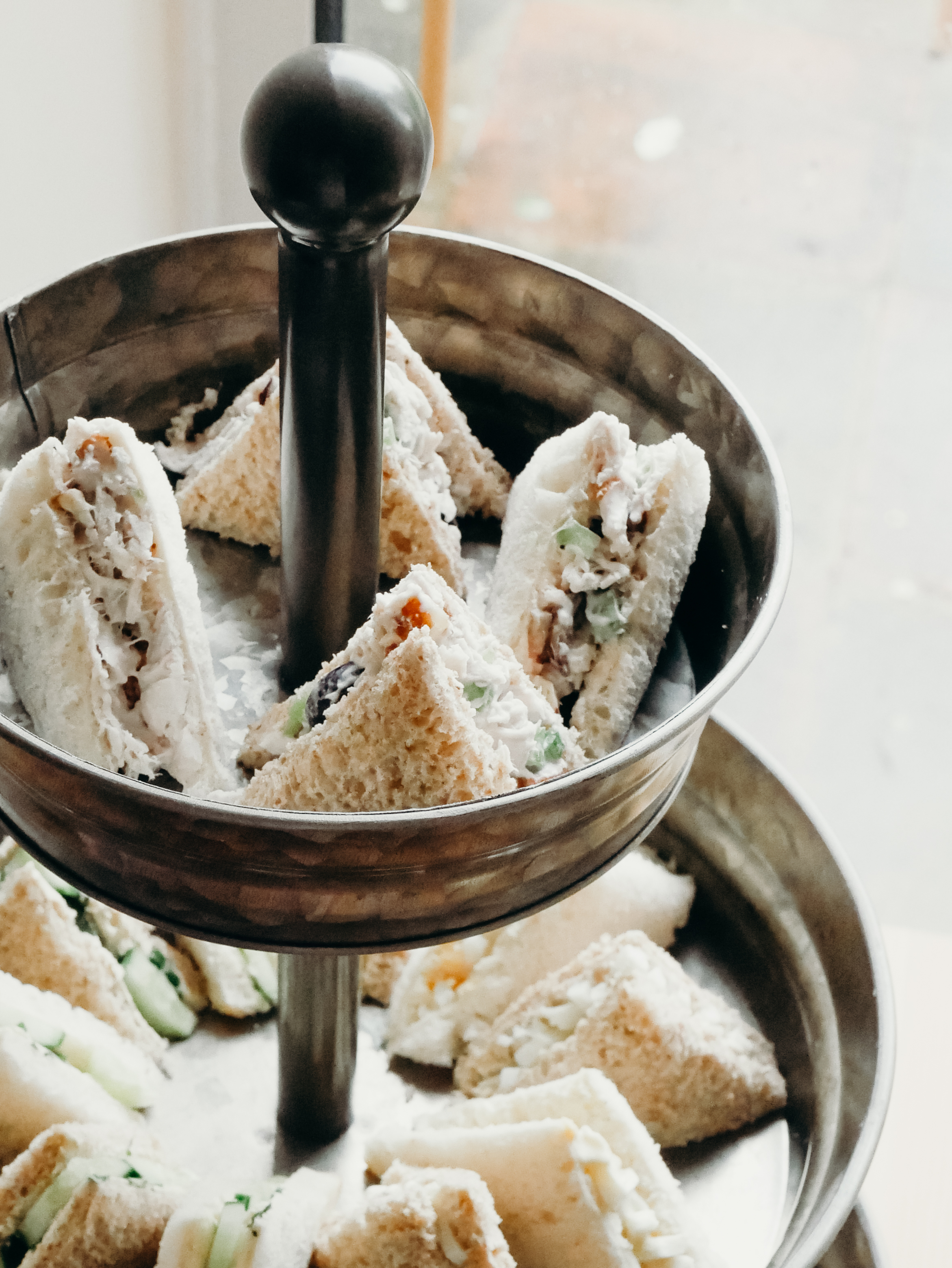 CHICKEN SALAD SANDWICHES - Taylor made the chicken salad with grapes and walnuts. (The original recipe calls for pecans.) We made all of the sandwiches on both wheat and white bread. I recommend getting as close to rectangular loaves as possible, otherwise you're cutting off a lot of top crust where it's uneven. Tea sandwiches always have the crust removed and are cut into thirds or fourths. I cut an X into the sandwiches, which made for two different sized triangles. I wish I had just cut them all into three strips (from top to bottom).