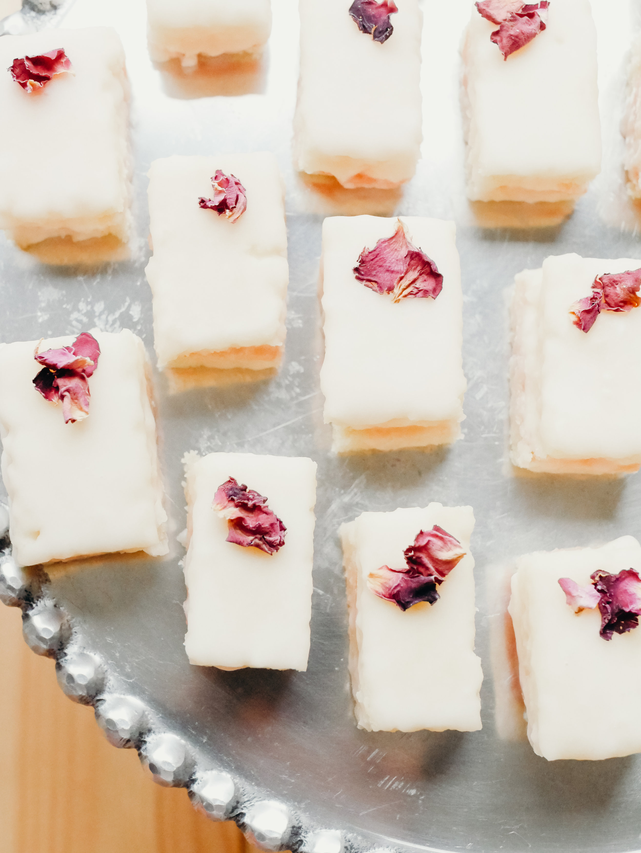 ROSE & ELDERFLOWER PETIT FOURS - Of course I turned to Sally's Baking Addiction for a simple petit fours recipe, though I did make some tweaks. Instead of making a lemon cake, I flavoured the batter with 1 tablespoon of rose water (this replaced the 3 tablespoons of lemon juice in the recipe). Her step-by-step instructions and corresponding video were really helpful, but I decided to make the petit fours with just a single layer of filling, spreading rose and elderflower curd on one side and the vanilla buttercream from the recipe on the other side. I wish I had measured out the cuts I made so they were more uniform, but they turned out okay. I used her Perfect Vanilla Icing recipe for the icing, colouring it with just a touch of pink food colouring. I scaled up the recipe to use 5 cups of confectioner's sugar and kept it vanilla so the rose wasn't too overpowering. I let the first coating dry before adding a second to help the colour pop on the cakes more. I topped them with edible rose petals before the second coat of icing was dry.