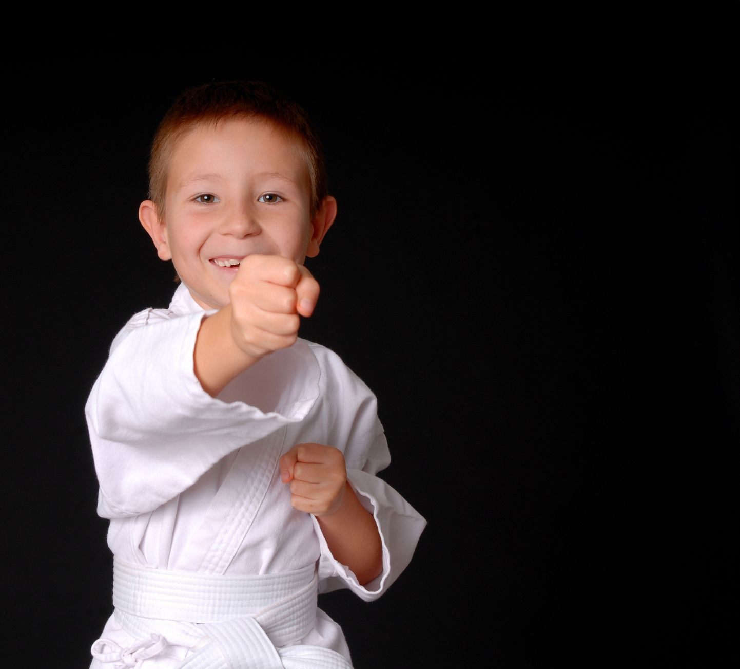 9014840 - young boy in karate outfit making fighting movement