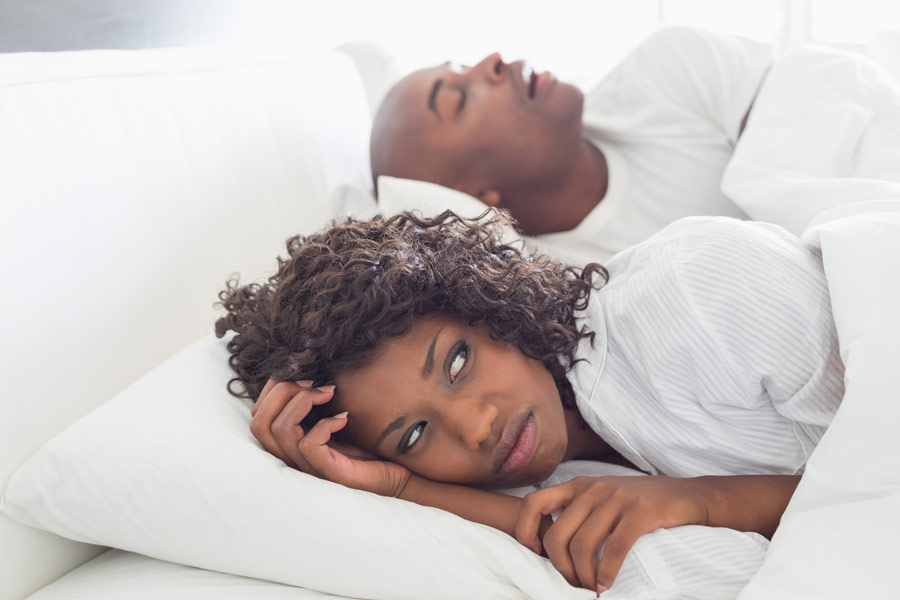 Female having interrupted sleep due to partner snoring