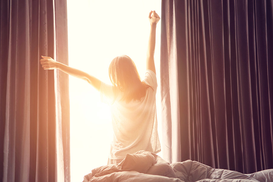 Woman waking up in the morning feeling rested after a good nights sleep