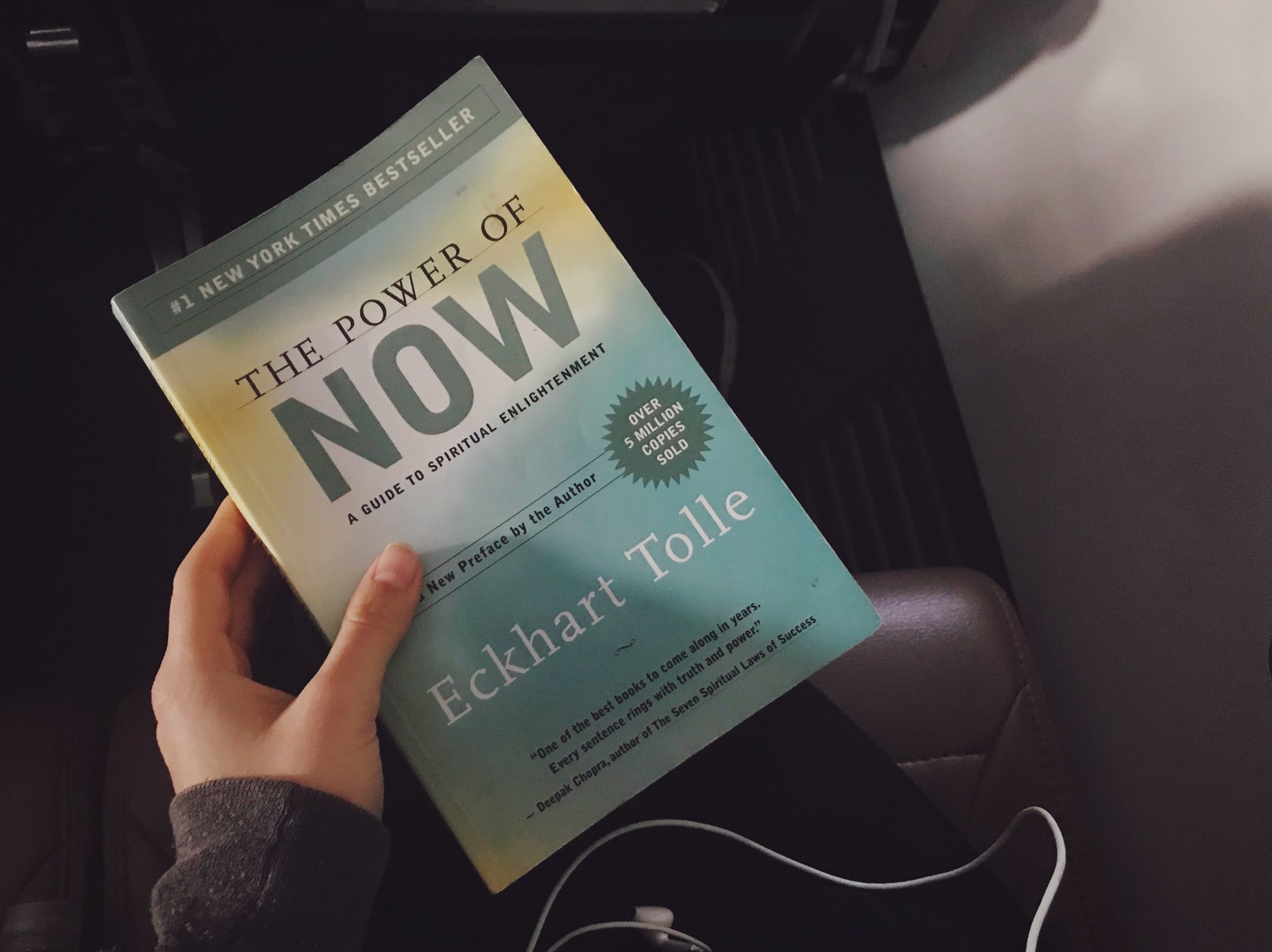 Plane reads:  The Power Of Now    by Eckhart Tolle