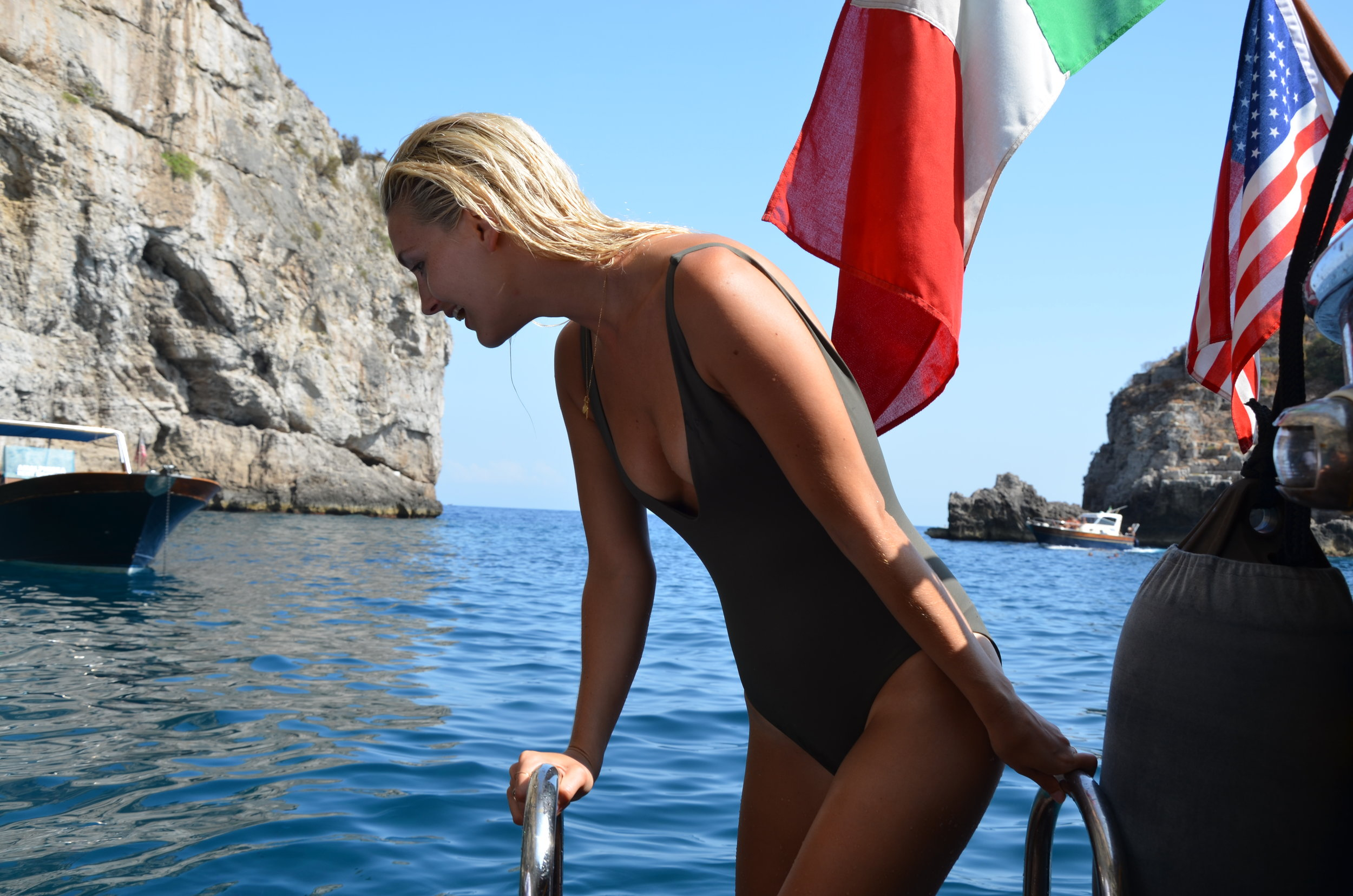 FEEDING THE FISH FROM THE BOAT IN  HER ONE-PIECE