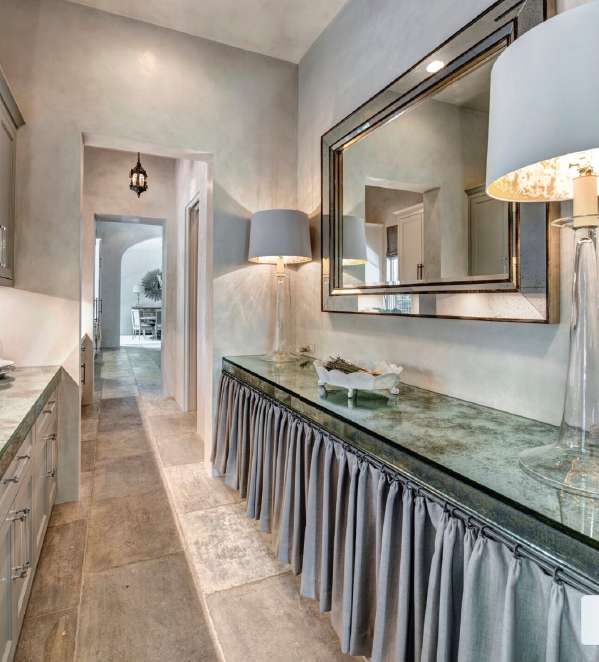 The glistening of mirrored glass counters married with aged stone floors and an antique lantern creates unexpected details and makes the room feel like you are unwrapping a present as you enter it. Photo by Michael Hunter