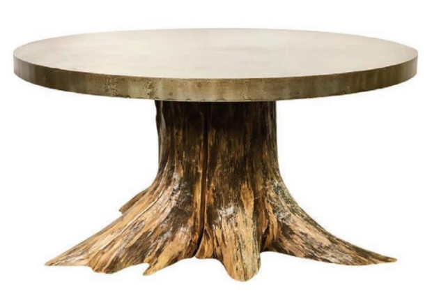 A truly unique and one-of-a-kind table, this piece features a wood stump recovered from the Mississippi River paired with the sheet steel made in India that has an antique pantina. Photography by Ashlee Nobel and courtesy of Paul Michael Company