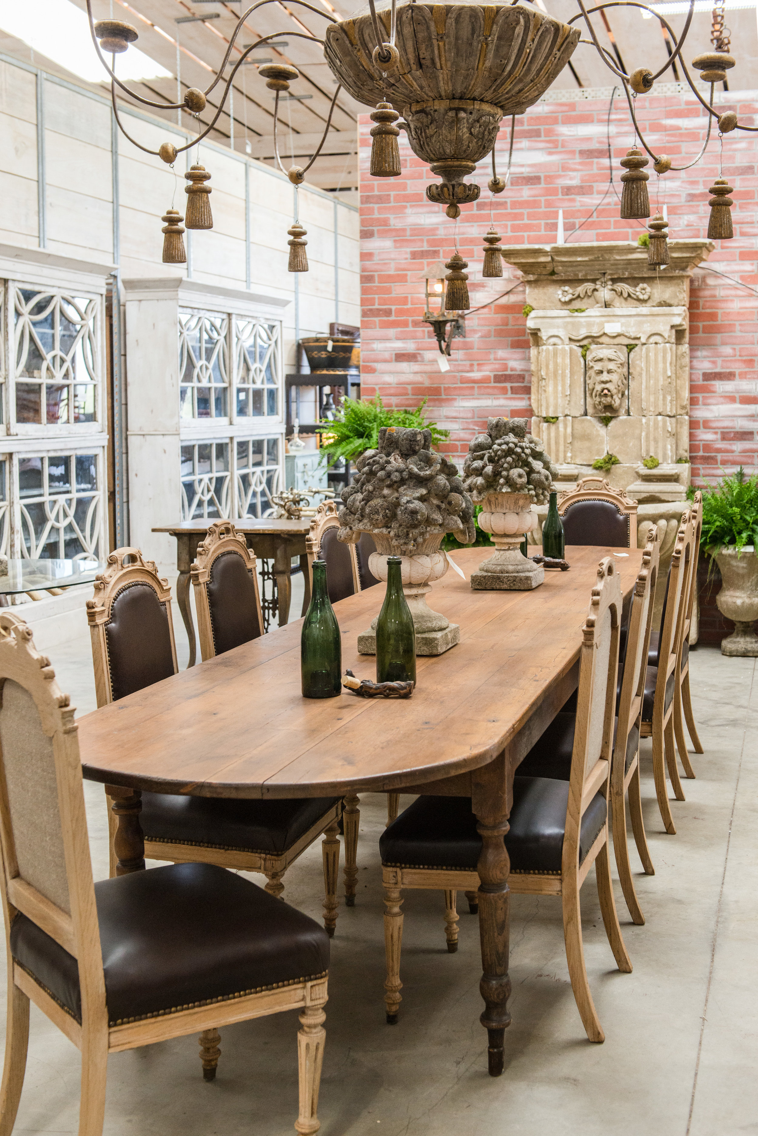 Rare 19th-century French elm and pine farmhouse table flanked with a set of 10 antique bleached oak and leather dining chairs.