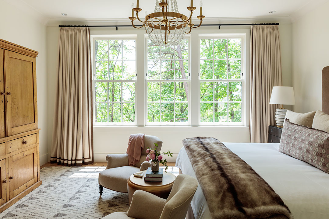 Photo by The Ingalls  Master bedroom of a private residence on the rental program with mountain views, antique case pieces and upholstery, Frette bedding and Visual Comfort lighting.