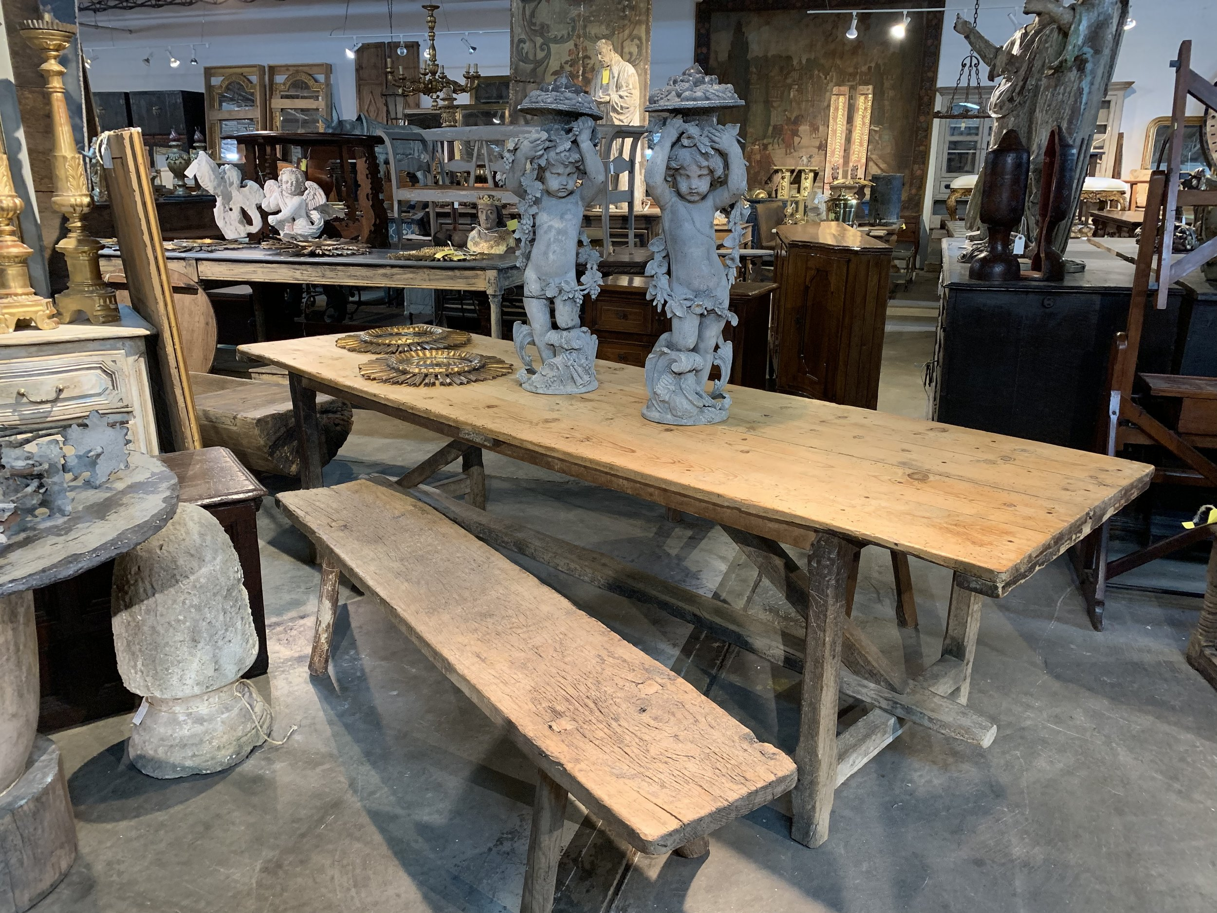 Photos courtesy of Provenance Antiques  A French 18th-century primitive farm table with benches with a pair of 19th-century zinc Putti from the Provence region of France