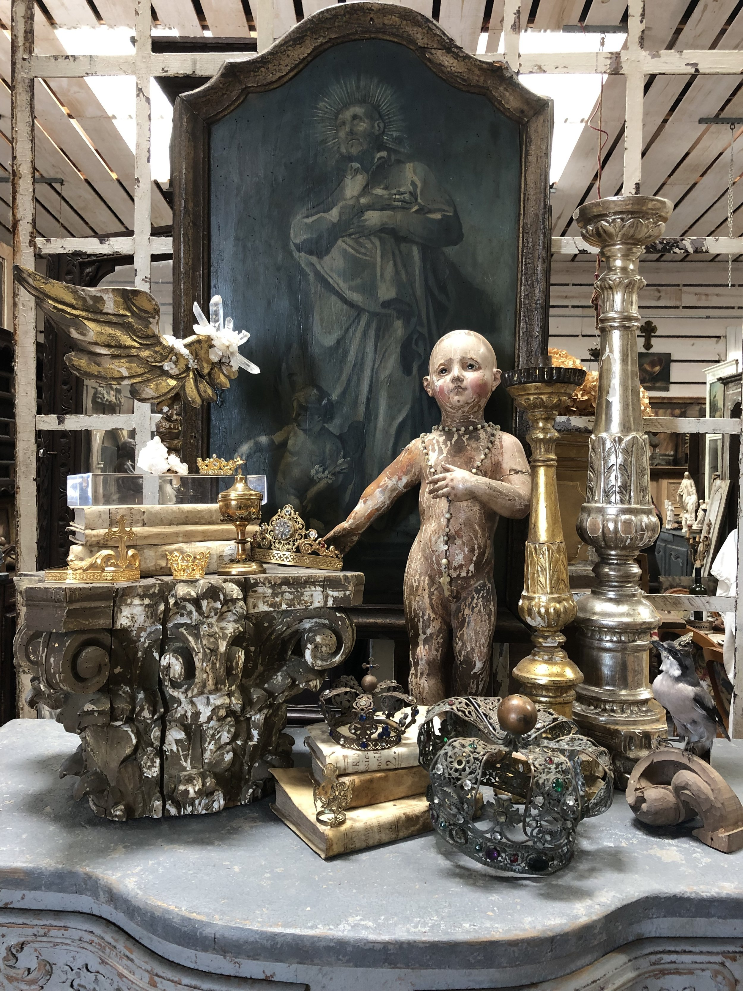 An 18th-century Italian Christ Child is surrounded by treasures found on the latest buying trip. Antique crowns, altar sticks, vellum books, and an 18th- century angel's wing mounted on a modern base come together to tell a story.