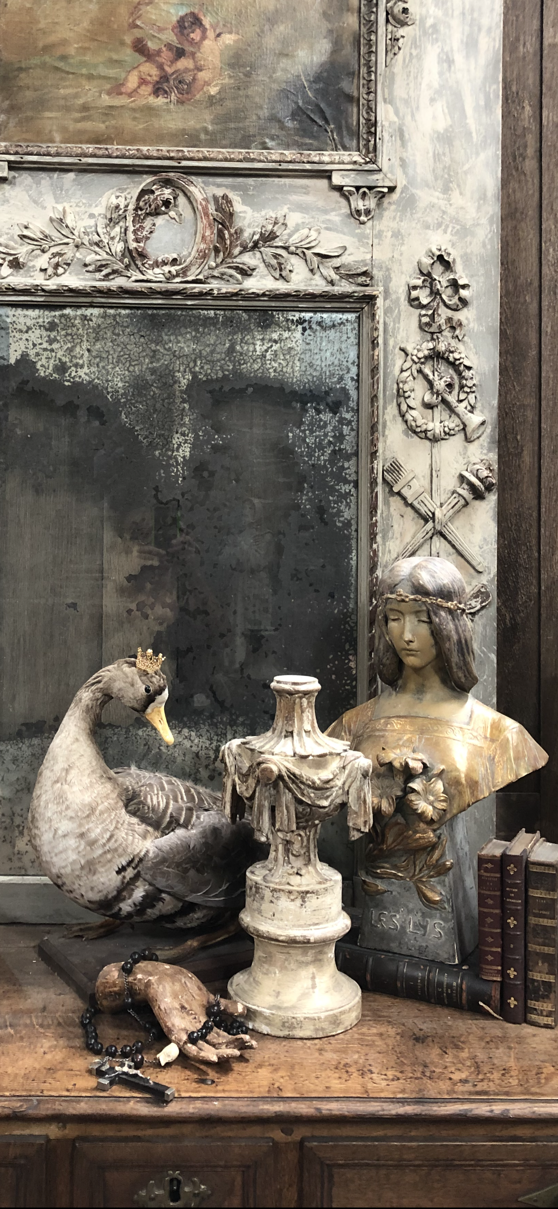 This monotone serene vignette includes a crowned French taxidermy duck which looks over its shoulder at a terra cotta art nouveau bust, a carved Italian finial, and an 18th-century saint's hand holding an early nun's rosary.