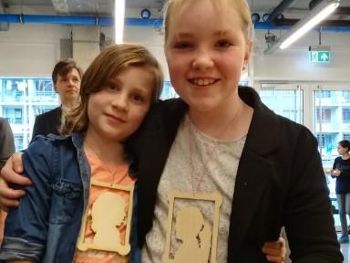 Kinderdirecteur Dominique van Hoof plus vriendin, met zelfgemaakte portretten om hun nek.