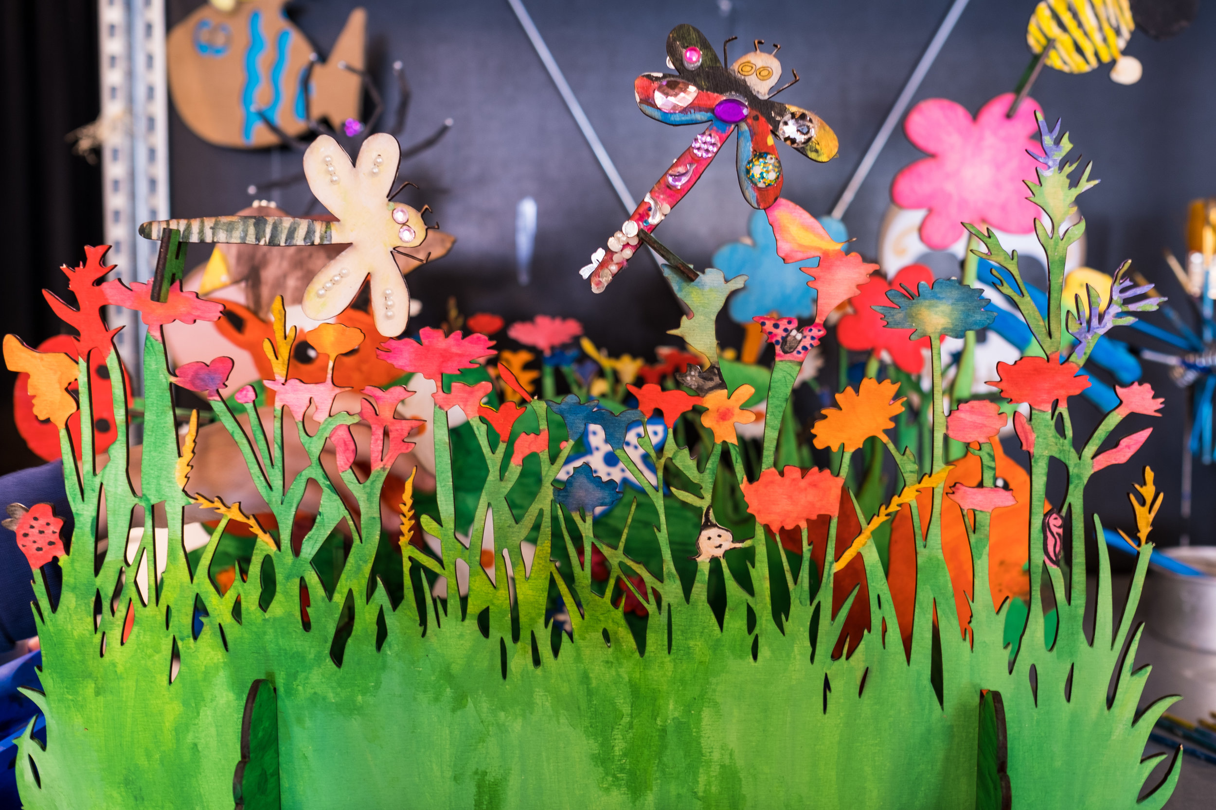 """De bloementuin   Fatima: """"Dit is de bloementuin die we hebben ontworpen. Elk kind in de maakplaats heeft een ander dier ervoor gemaakt. Je ziet bijvoorbeeld al twee libellen boven het gras."""""""