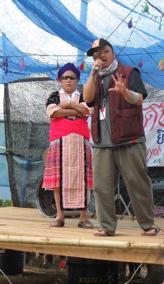 Tou SaiKo Lee raps while his grandma, Youa Chang, stands in teh background in Phu Chi Fa Mountain, Thailand. Photo credit: Phas Vwj.