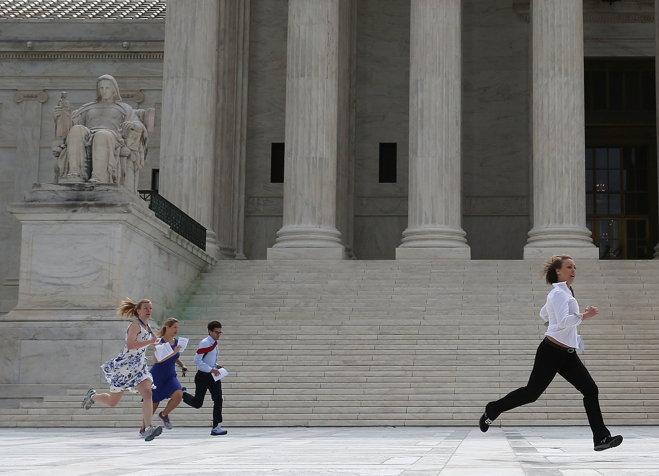 "Members of the media run across the plaza at the Supreme Court holding decisions on June 25, 2015, in an official tradition referred to as the ""running of the interns."" (AL DRAGO/CQ ROLL CALL/GETTY IMAGES)"