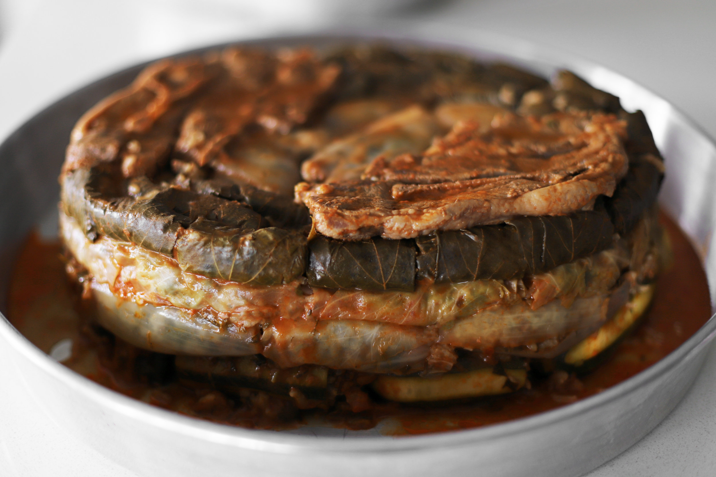 """Dolma khuitah (""""combination"""" dolma)    Dolma is enjoyed all over the Middle East, North Africa, and surrounding areas, and it's another one of those foods that's incredibly diverse. Depending on who's making it and what's being stuffed, one version will taste completely different from another. This is my grandmother's """"combination"""" dolma, which has a lot of grape leaves, cabbage leaves, and zucchini, and is simmered in vegetable juice. It's basically my favorite thing in the entire world."""