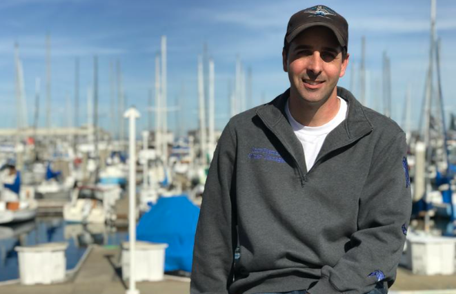 Fisherman Scott Fosmark sits on a railing in front of the Monterey Municipal Marina. With deep roots in Monterey's fishing heritage, he hopes the new fish hub can restore the area's local fish supply chain.  ERIKA MAHONEY